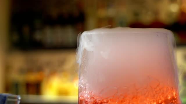 vidéos et rushes de barman mélange cocktail à boire verre au bar, près de main barman versant un alcool de boissons en verre - shaker