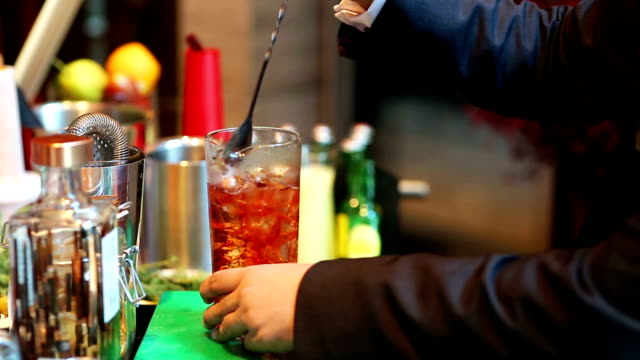 bartender mixing cocktail with drinking glass at bar, close up barman hand pouring a alcohol drinks into glass - mixing stock videos and b-roll footage