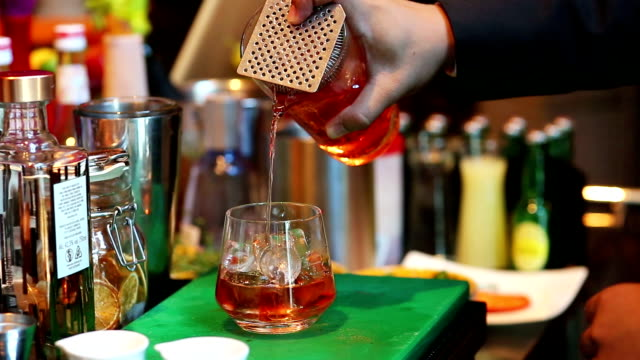 bartender mixing cocktail with drinking glass at bar, close up barman hand pouring a alcohol drinks into glass - rum stock videos and b-roll footage