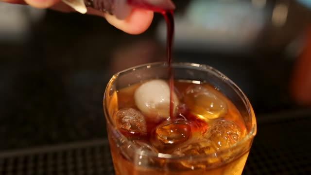 vidéos et rushes de barman mélangeant le cocktail délicieux sur le compteur de barre avec la cuillère dans la boîte de nuit - shaker