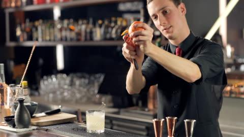 stockvideo's en b-roll-footage met barman peeling een sinaasappel voor cocktail garren - pellen