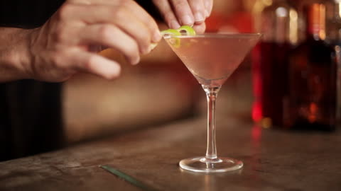 bartender placing twist of lime rind on rim of martini glass - alcohol drink stock videos & royalty-free footage