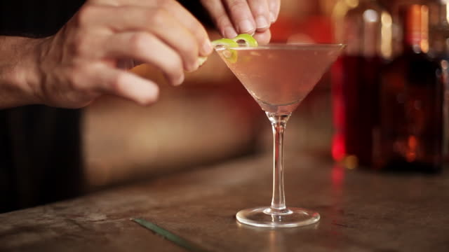 bartender placing twist of lime rind on rim of martini glass - twisted stock videos & royalty-free footage
