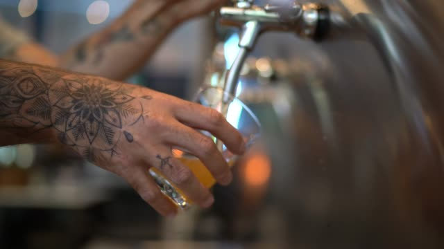bartender pouring beer from beer tap at bar - tattoo stock videos & royalty-free footage