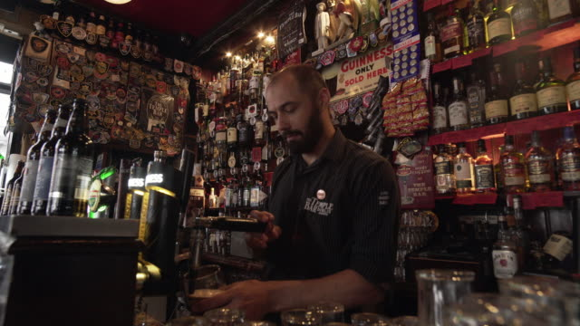 bartender pouring beer from tap in dublin temple bar pub - dublin ireland stock videos and b-roll footage