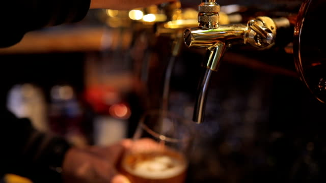 bartender pouring beer in beer glass - pint glass stock videos & royalty-free footage