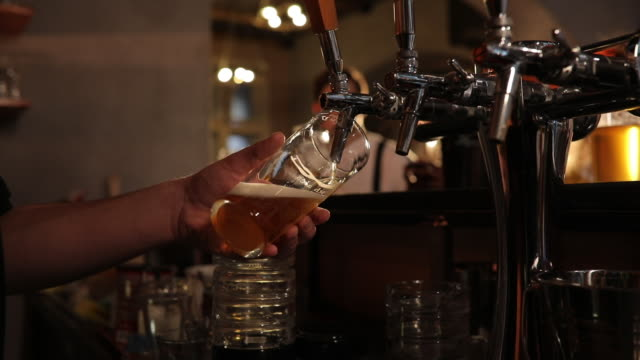 bartender pouring beer in pub - frothy drink stock videos and b-roll footage
