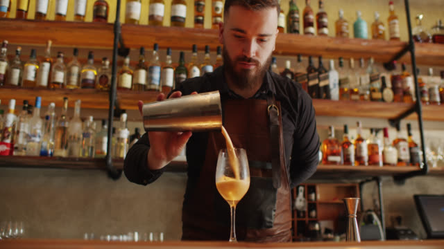 bartender pouring cocktail from shaker to glass - cocktail stock videos & royalty-free footage