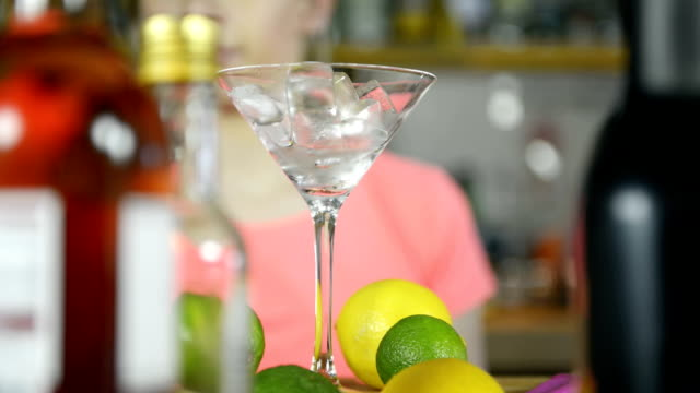 bartender pouring cocktail into glass - martini glass stock videos & royalty-free footage