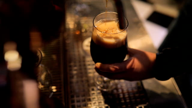 bartender pouring dark beer in pub - serving food and drinks stock videos & royalty-free footage