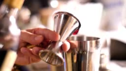 Bartender pouring drink into shaker, slowmotion footage