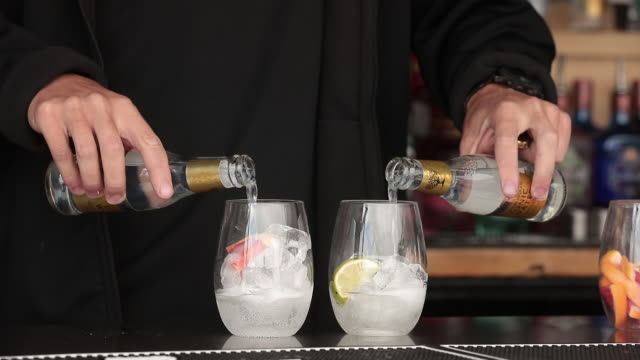 bartender pouring fever-tree tonic water into glasses at cowes week on isle of wight, england, uk, on tuesday, august 13, 2019. - tonic water stock videos & royalty-free footage
