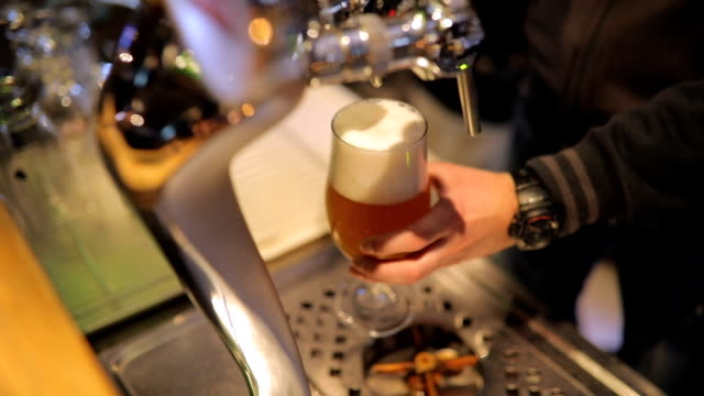 bartender pouring fresh beer - bartender stock videos and b-roll footage