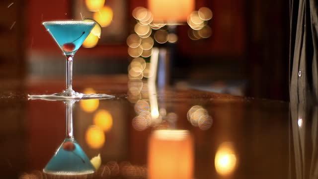 vidéos et rushes de a bartender pours a blue martini. - shaker