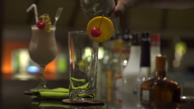 a bartender pours a tropical drink at a bar at a resort. - tropical drink stock videos & royalty-free footage