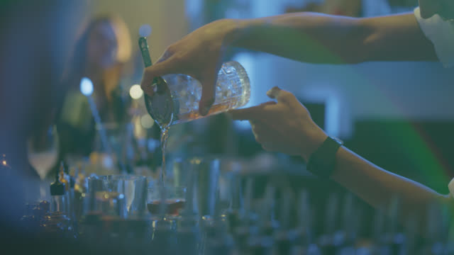 bartender pours alcohol from a glass and a cocktail shaker into a drink - drink stock videos & royalty-free footage