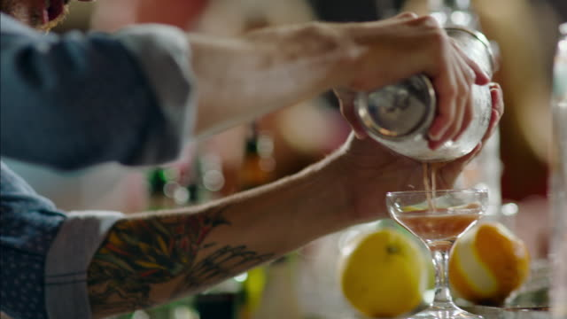 vidéos et rushes de bartender pours beautiful handcrafted mixed drink into cocktail glass - shaker