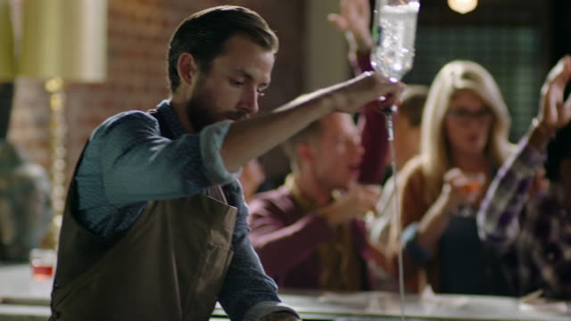 bartender pours drink as group of friends dance at bar - cocktail stock-videos und b-roll-filmmaterial