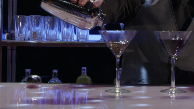 CU bartender pours drinks and camera pans to young couple who mingle and toast - nightclub bar scene