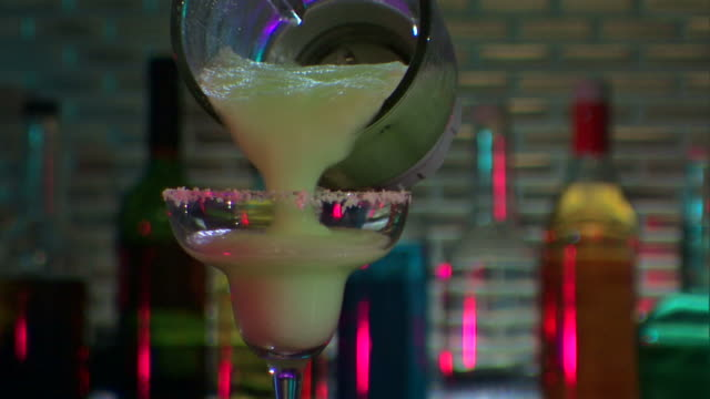 bartender pours margarita into salted glass. - margaritas stock videos and b-roll footage