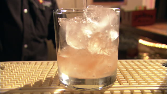a bartender pours rum over ice in a rocks double old fashioned glass. - rum stock videos and b-roll footage