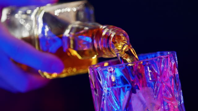bartender pours whiskey in a glass and haves gold reflection of light on the edges. close up on a blue background. - refreshment stock videos & royalty-free footage