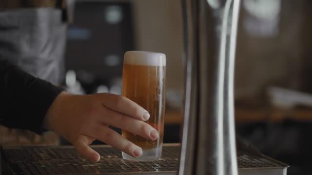 vídeos y material grabado en eventos de stock de camarero preparando y vertiendo un vaso de cerveza - sólo hombres