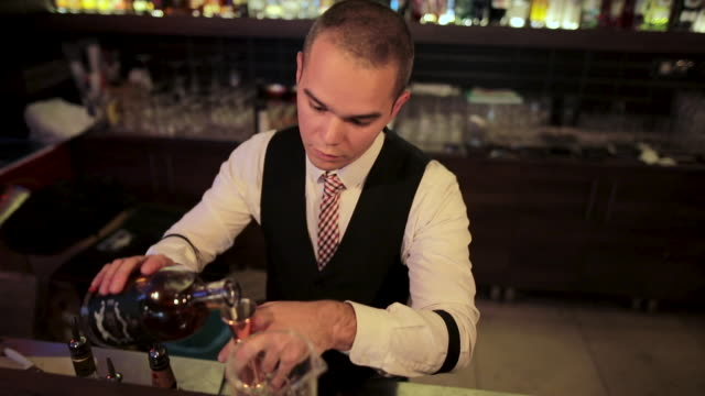 bartender preparing and pouring alcoholic cocktail drink at bar - ice cube stock videos & royalty-free footage