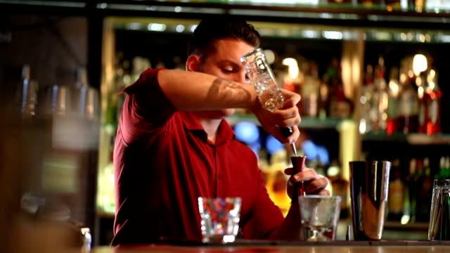 vidéos et rushes de cocktail de préparation de barman - shaker