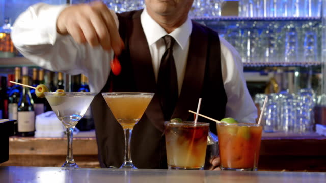 stockvideo's en b-roll-footage met ms tu bartender preparing mixed drinks places empty martini glass on bar counter and pours drink from shaker into glass and drops maraschino cherry into the glass - martiniglas