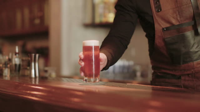 bartender putting down a drink on the bar counter - beer glass stock videos & royalty-free footage
