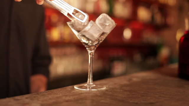 Bartender putting ice cubes into martini glass