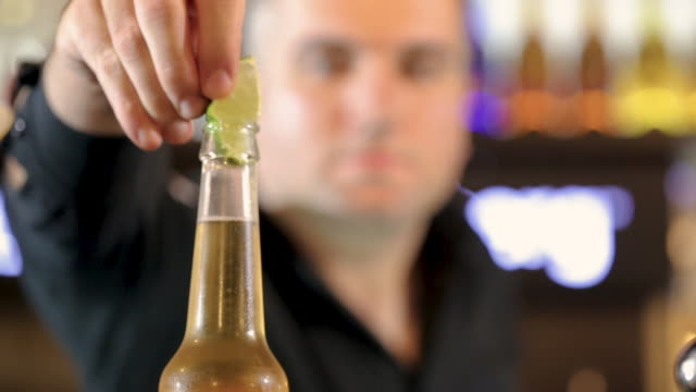 bartender putting lime wedge in bottle of cold craft beer, close-up - lime stock videos & royalty-free footage