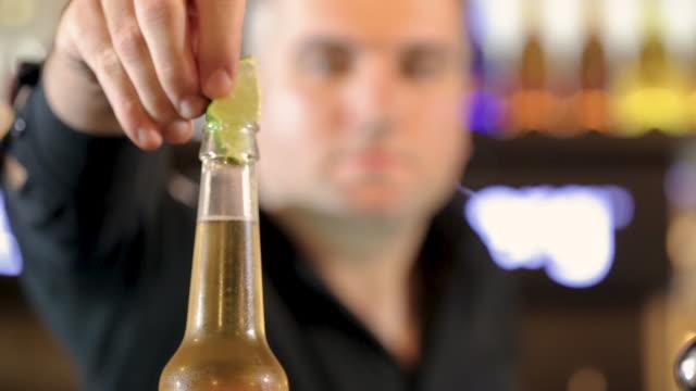 バーテンダーはコールドクラフトビールのボトルにライムウェッジを入れ、クローズアップ - ライム点の映像素材/bロール