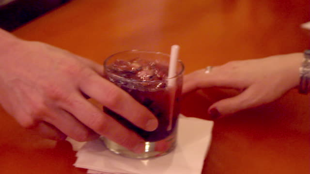 A bartender serves a mixed drink at the bar.