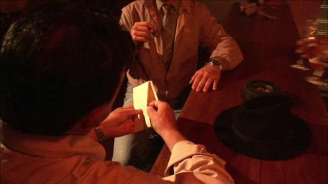 A bartender serves wine to two patrons at the bar after one of the men gives an envelope of money to the other.