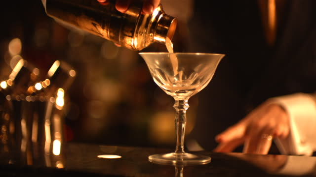 ms slo mo r/f bartender serving his cocktail in glass / united kingdom - hotel stock-videos und b-roll-filmmaterial