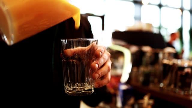 オレンジジュースを提供するバーテンダー - オレンジジュース点の映像素材/bロール