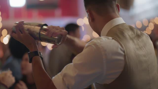 vidéos et rushes de bartender shakes a cocktail shaker while making cocktails at a bar - shaker