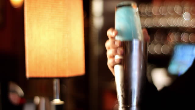 a bartender shakes a martini. - shaking stock-videos und b-roll-filmmaterial