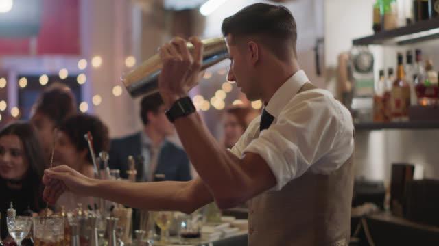 vidéos et rushes de bartender shakes cocktail shaker and stirs drink at the same time - shaker