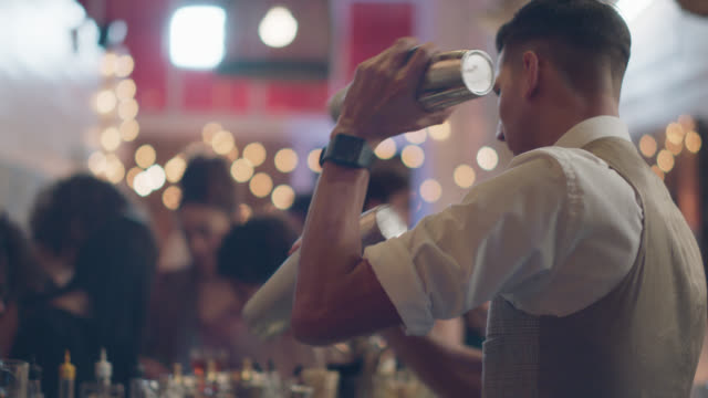 bartender shakes two cocktail shakers at the same time - bartender stock videos & royalty-free footage
