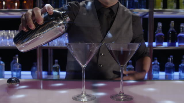 CU bartender shaking and pouring drinks into martini glasses at a nightclub bar