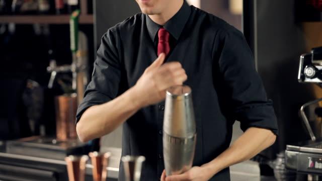 vidéos et rushes de barman secouant et tournant le shaker de cocktail - shaker