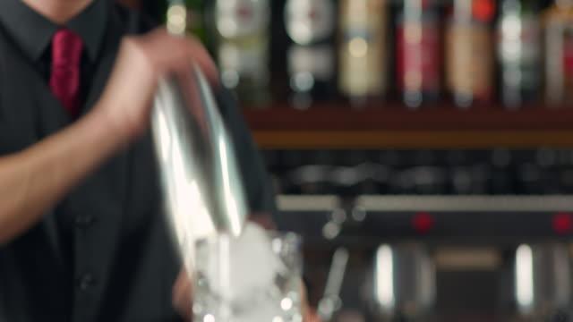 vidéos et rushes de cocktail de secouant de barman et préparant le verre à boire - shaker