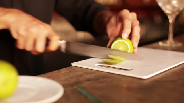 Bartender slicing limes for use in cocktail