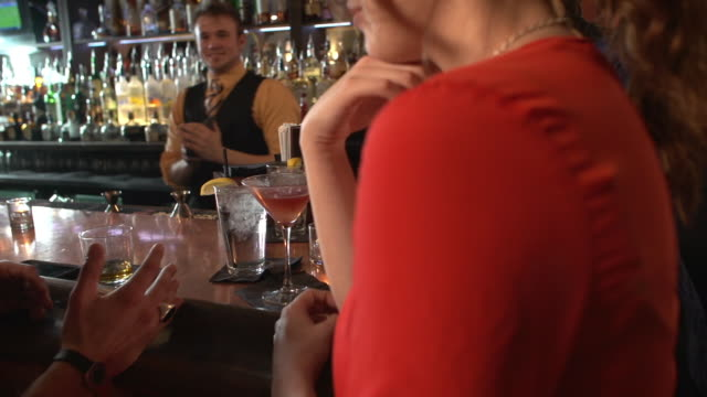 bartender sliding water cocktail to woman at bar