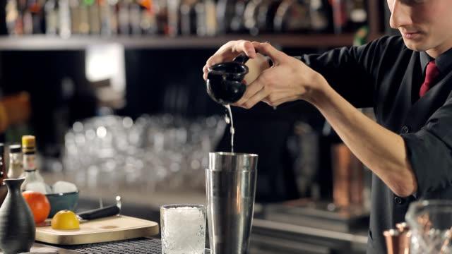vidéos et rushes de barman serrant le jus de citron, utilisant le sqeezer de main - shaker