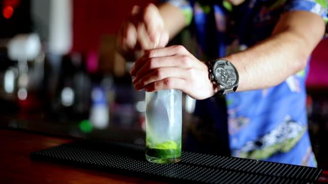 Bartender stirring cucumber mojito