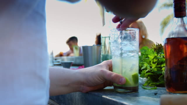 stockvideo's en b-roll-footage met barman roeren drankje op outdoor pool party - cocktail